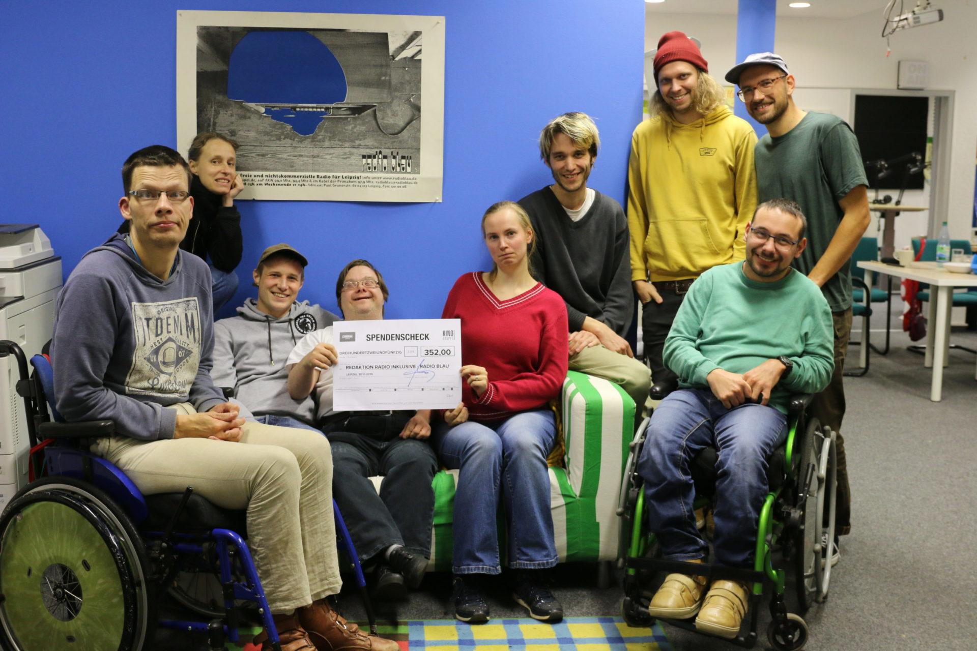 Ein Foto der Redaktionsmitglieder. 9 Personen. Zwei halten einen Spendencheck hoch.