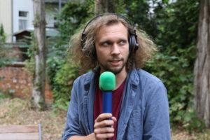 Das Bild zeigt Redaktionsmitglied Arne mit einem Mikrofon in der Hand und Kopfhörern auf den Ohren