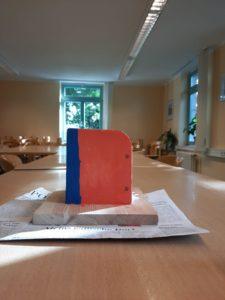 Der Kartonhalter von der Seite fotografiert. Er ist in den Farben blau und rot bemalt und steht zum trocknen auf eienr auf dem Tisch ausgebreiteten Zeitung