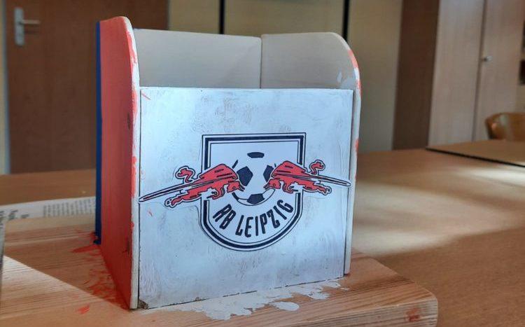 Ein Foto des im Artikel beschriebene Hilfsmittels aus Holz verziehrt mit dem Logo von RB Leipzig