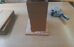 Zu sehen ist das Hilfsmittel im Einsatz. Der kleine Holzkasten ist in RB-Farben angemalt. Er steht auf einem Tisch. Der Karton lässt sich zum Falten darüber stülpen.